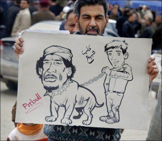 Manifestante segura cartaz com caricatura do ditador Muammar Gaddafi